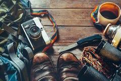 Accessori di viaggio su fondo di legno, vista superiore Vecchi stivali di cuoio d'escursione, zaino, macchina da presa d'annata e fotografia stock