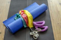 Accessori domestici di forma fisica sulla stuoia di yoga Fotografia Stock