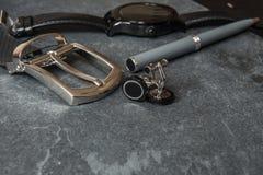 Accessori eleganti di affari del ` s degli uomini Orologi del nero, cinghia, penna, gemelli sulla tavola di pietra di lusso  Fotografia Stock