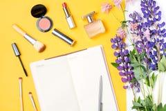 Accessori moderni della donna Prodotti di bellezza, taccuino, accessori, fiori su un fondo pastello Fotografie Stock