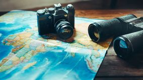 Accessori per la macchina da presa d'annata, la mappa ed il binocolo di viaggio sulla Tabella di legno, Front View Esploratore Jo immagini stock libere da diritti
