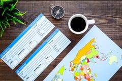 Accessori per treveling con la carta dei biglietti, della mappa e del caffè sulla vista superiore del fondo di legno della scriva Fotografia Stock Libera da Diritti