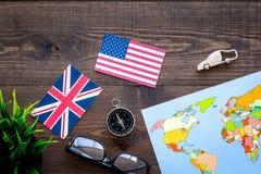 Accessori per treveling con la mappa e le bandiere sulla vista superiore del fondo di legno della scrivania Immagine Stock Libera da Diritti
