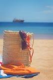 Accessori prendenti il sole nella borsa della paglia Fotografie Stock