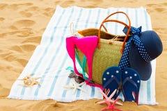 Accessori prendenti il sole sulla spiaggia sabbiosa Fotografie Stock