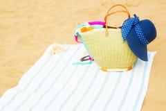 Accessori prendenti il sole sulla spiaggia sabbiosa Immagini Stock