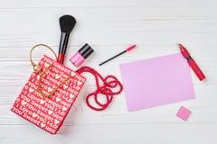 Accessori rossi di trucco e del sacchetto della spesa Fotografia Stock