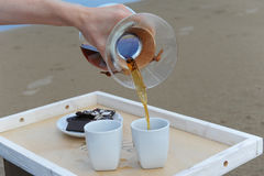 Accessories for alternative brewing coffee on a tray on the sandy beach. Barista spills coffee on cups. Accessories for alternative brewing coffee on tray on the Stock Photography
