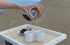 Accessories for alternative brewing coffee on a tray on the sandy beach. Barista spills coffee on cups Stock Photos