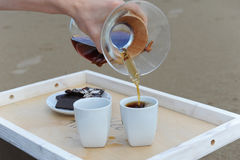 Accessories for alternative brewing coffee on a tray on the sandy beach. Barista spills coffee on cups Stock Photo