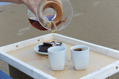 Accessories for alternative brewing coffee on a tray on the sandy beach. Barista spills coffee on cups. Accessories for alternative brewing coffee on tray on the Stock Photo