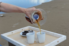 Accessories for alternative brewing coffee on a tray on the sandy beach. Barista spills coffee on cups. Accessories for alternative brewing coffee on tray on the Stock Image