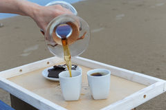 Accessories for alternative brewing coffee on a tray on the sandy beach. Barista spills coffee on cups. Accessories for alternative brewing coffee on tray on the Royalty Free Stock Images