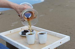 Accessories for alternative brewing coffee on a tray on the sandy beach. Barista spills coffee on cups. Accessories for alternative brewing coffee on tray on the Stock Images