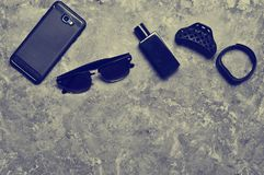 Accessories for a business woman on a concrete table. Purse, perfume, sunglasses, smart watch, smartphone, pen. Working space. Monochrome photography. Trend of stock photos