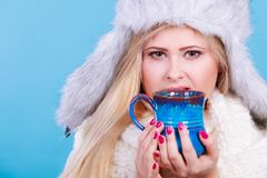 Blonde woman in winter furry hat drinking. Accessories and clothes for cold days, fashion concept. Blonde woman in winter warm furry hat drinking hot drink from Stock Photography