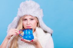 Blonde woman in winter furry hat drinking Stock Photos