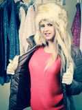 Woman picking winter outfit in wardrobe. Accessories and clothes for cold days, fashion concept. Blonde woman in winter warm furry hat and jacket, standing in Stock Photography