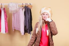Woman picking winter outfit in wardrobe. Accessories and clothes for cold days, fashion concept. Blonde woman in winter warm furry hat and jacket, standing in Stock Photo