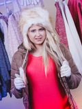 Woman picking winter outfit in wardrobe. Accessories and clothes for cold days, fashion concept. Blonde woman in winter warm furry hat and jacket, standing in Royalty Free Stock Images