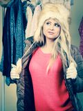 Woman picking winter outfit in wardrobe. Accessories and clothes for cold days, fashion concept. Blonde woman in winter warm furry hat and jacket, standing in Royalty Free Stock Photos