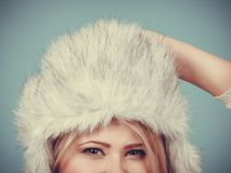 Blonde woman in winter furry hat. Accessories and clothes for cold days, fashion concept. Blonde woman in winter warm furry hat in russian style Stock Photo