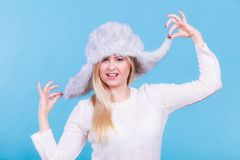 Blonde woman in winter furry hat. Accessories and clothes for cold days, fashion concept. Happy blonde woman in winter warm furry hat in russian style Stock Photos