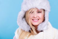 Blonde woman in winter furry hat. Accessories and clothes for cold days, fashion concept. Happy blonde woman in winter warm furry hat in russian style Stock Image