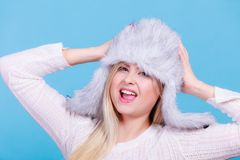 Blonde woman in winter furry hat. Accessories and clothes for cold days, fashion concept. Happy blonde woman in winter warm furry hat in russian style Royalty Free Stock Images