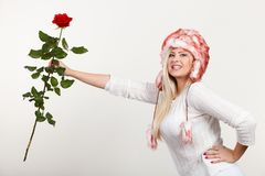 Woman in winter furry hat holding red rose. Accessories and clothes for cold days, fashion, romantic gestures concept. Woman in winter furry hat holding red rose Stock Photo