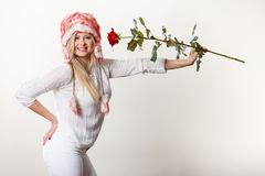 Woman in winter furry hat holding red rose. Accessories and clothes for cold days, fashion, romantic gestures concept. Woman in winter furry hat holding red rose Stock Photos