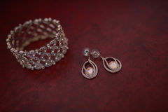 Thick semi-precious bracelet and matching hanging earrings displayed on a dark, burgundy mat. Accessories, concepts, details, ideas and themes, bride morning Royalty Free Stock Photo