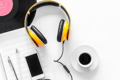Accessories of contemporary composer. Headphones. phone, vinyl record, music notes on white background top view Stock Image