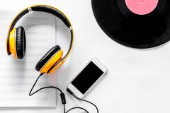 Accessories of contemporary composer. Headphones. phone, vinyl record, music notes on white background top view Royalty Free Stock Images