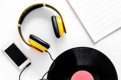 Accessories of contemporary composer. Headphones. phone, vinyl record, music notes on white background top view Stock Photo