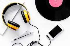 Accessories of contemporary composer. Headphones. phone, vinyl record, music notes on white background top view Stock Photography