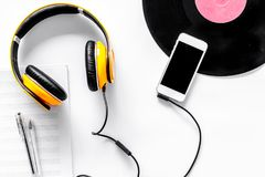 Accessories of contemporary composer. Headphones. phone, vinyl record, music notes on white background top view Royalty Free Stock Photo