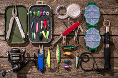 Accessories for fishing on the background of wood. Top view. Accessories for fishing on the background of wood. Reel, fishing line, float, net hooks, lures for stock image