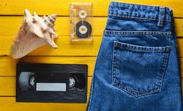 Accessories x generation: jeans, audio cassette, vhs, shell on a wooden table of yellow color. Summer concept. Top view. Accessories x generation: jeans, audio Stock Photos
