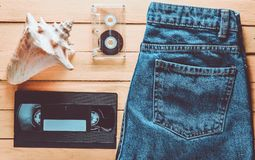 Accessories x generation: jeans, audio cassette, vhs, shell on a. Wooden table of yellow color. Summer concept. Top view stock image