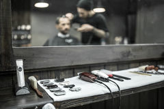 Accessories of hairdresser in barbershop. Hairdressing accessories on the white towel on the wooden rack in the barbershop. There is a blurry reflection of a stock photo
