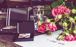 Accessories for the a make up and roses on the table Stock Photography