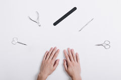 Accessories for manicure lie around a female hands on a white ta stock images