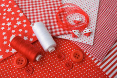 Accessories for sewing in red-white co. Accessories for sewing: threads, fabric, buttons in red-white color Stock Photo