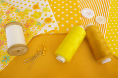 Accessories for sewing in yellow-white. Accessories for sewing: threads, fabric, buttons in yellow-white color Stock Images