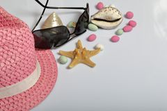 Accessories for summer holidays. Hat and sunglasses on a white background. Near colored pebbles, seashells and starfish.  stock photography