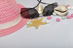 Accessories for summer holidays. Hat and sunglasses on a white background. Near colored pebbles, seashells and starfish.  stock image
