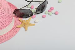 Accessories for summer holidays. Hat and sunglasses on a white background. Near colored pebbles and starfish.  royalty free stock images