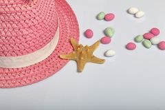 Accessories for summer holidays. Hat on a white background. Near colored pebbles and starfish.  stock photos