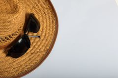 Accessories for summer holidays. Straw hat and sunglasses. On a white background.  royalty free stock image